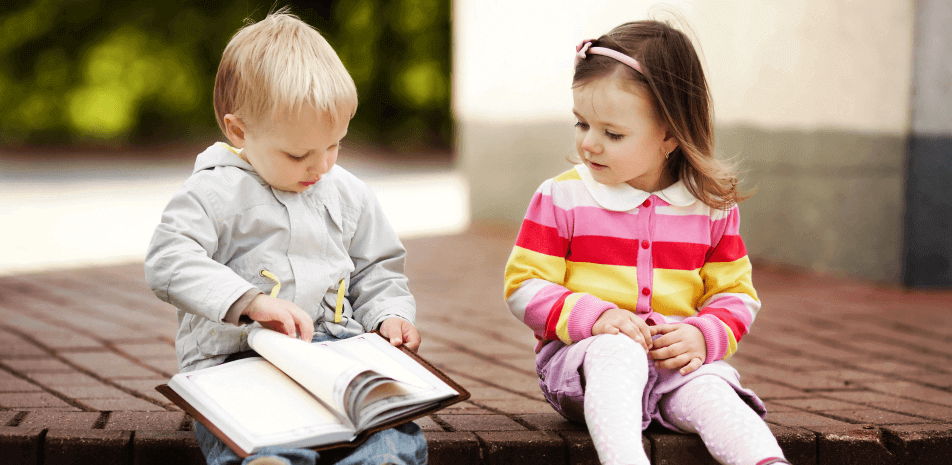 girl and boy sitting while reading